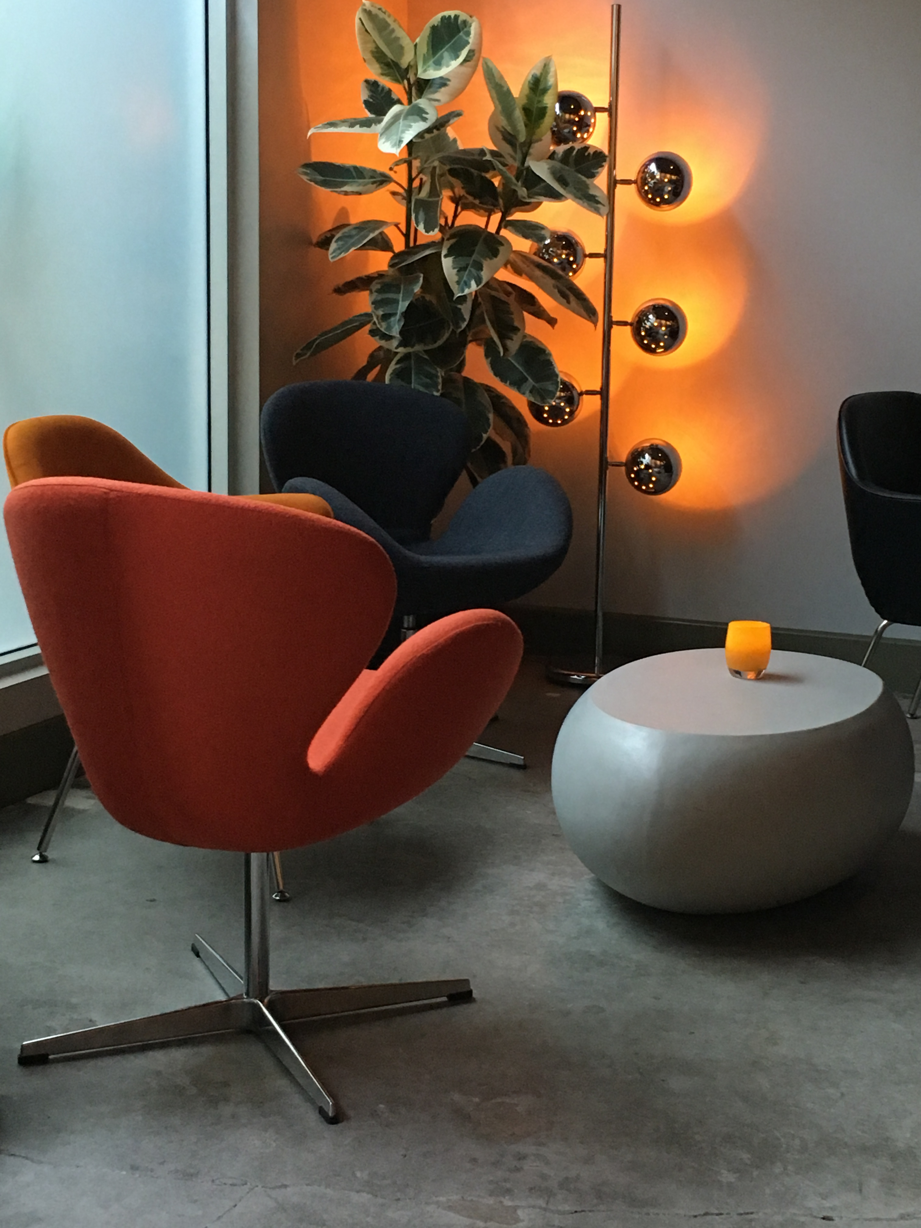 A photo of hip orange and navy chairs by a cool looking candle and a sleek lamp at local bar Honcho in downtown Los Altos, California. Photo Courtesy of FoodWaterShoes