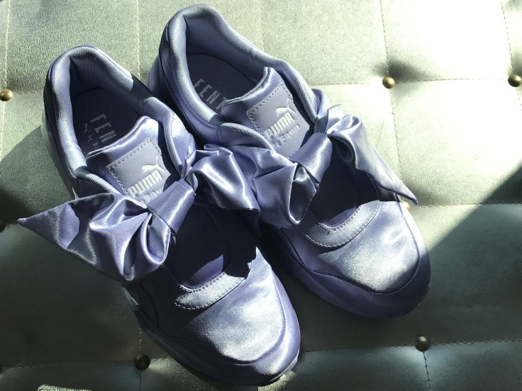 A Pair of Purple Lavender Sneakers with Bows on a Silver Background