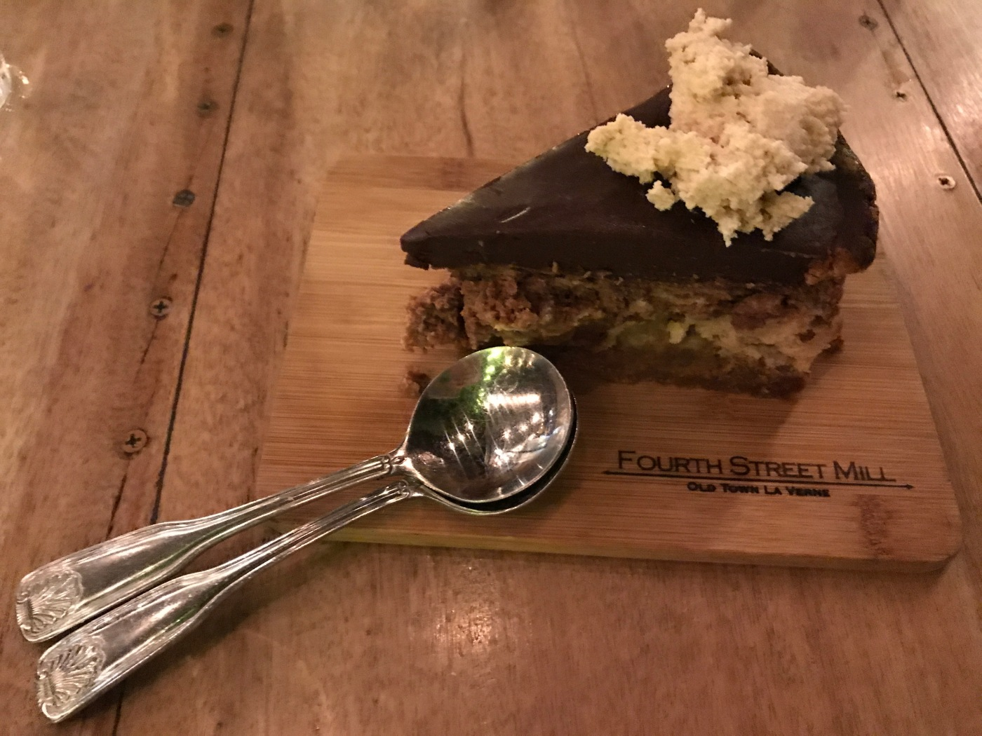 A Slice of Chocolate Peanut Butter Cheesecake Sits Beside Two Spoons at Fourth Street Mill in La Verne, California