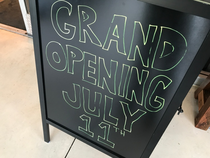 A Grand Opening July 11th Sign Sits on the Sidewalk Outside of Scrambl'z Restaurant on The Alameda in San Jose, California