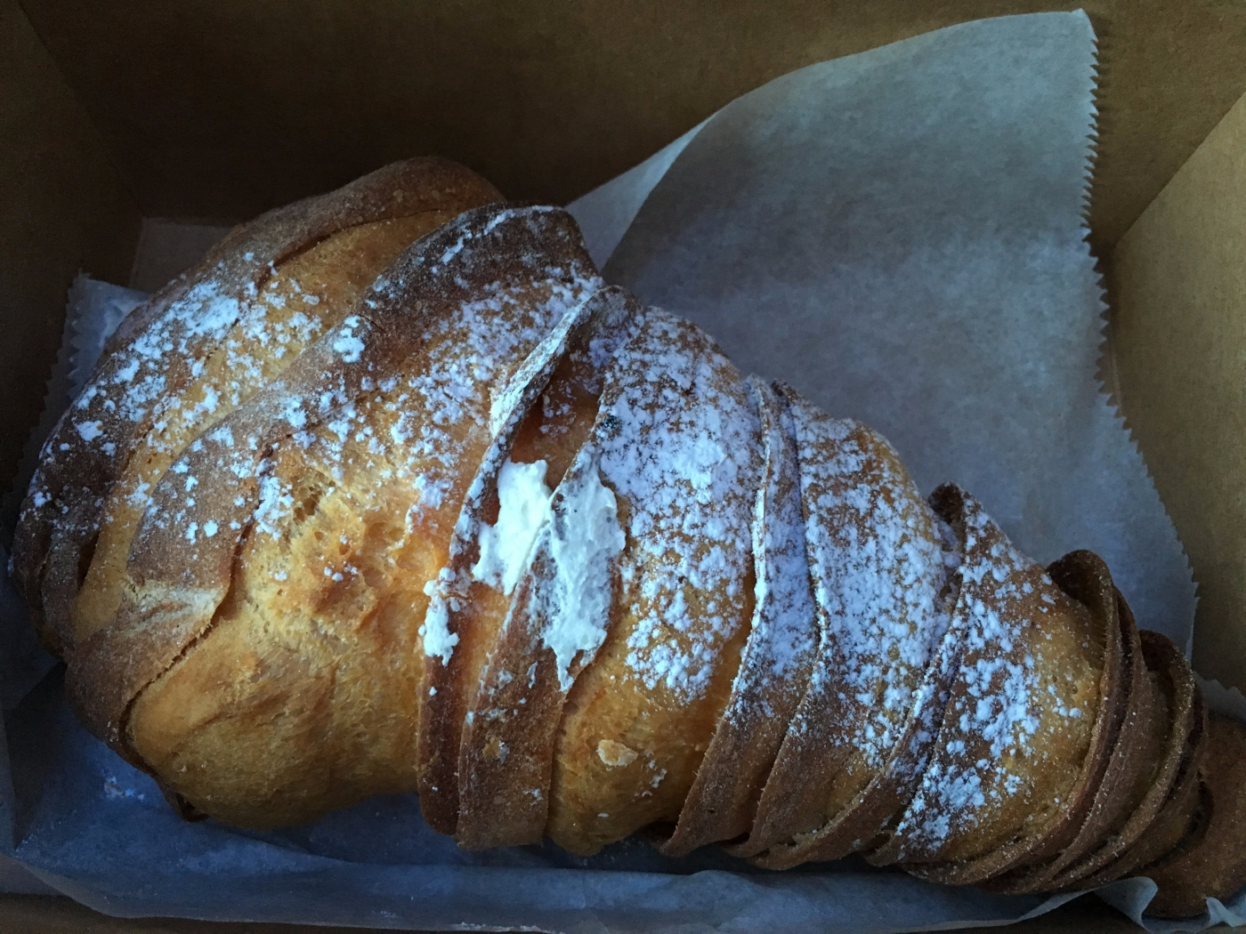 A Giant Lobster Tail Donut with Powdered Sugar from Mike's Pastry in Boston, Massachusetts