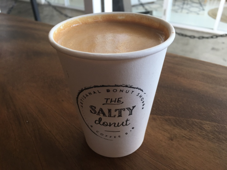 A Cup Filled with a Cinnamon Toast Crunch Latte at The Salty Donut in Miami's Wynwood Art District Sits on a Table