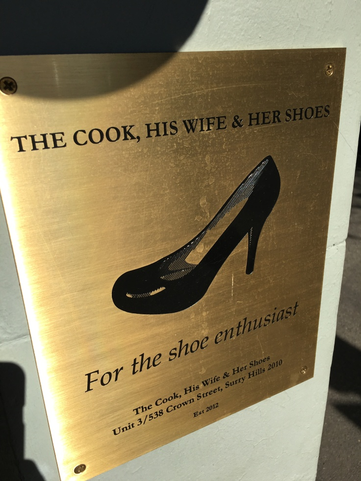"A Gold Sign Outside of The Cook, His Wife & Her Shoes Shop that Says, ""For the Shoe Enthusiast."""