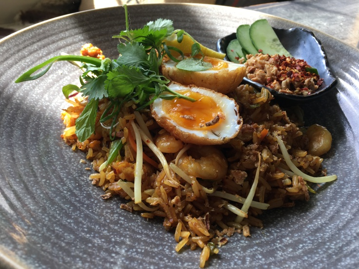 Nasi Goreng Made with Fried Fragrant Jasmine Rice, Tiger Prawns, Free Range Chicken, Chili, Shallots, Bean Sprouts, Peanuts and a Son-in-Law Egg