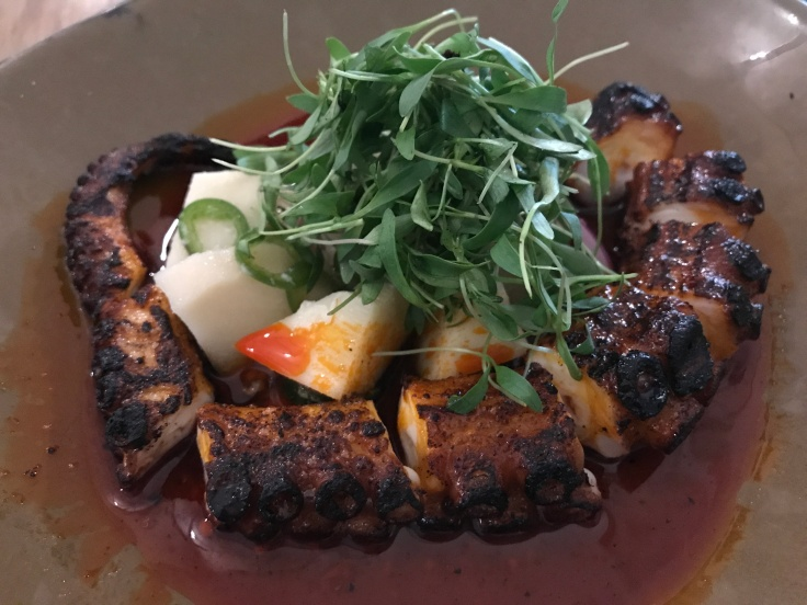 Grilled Octopus at KYU Restaurant in Miami, Florida Served with Hearts of Palm and Red Onion