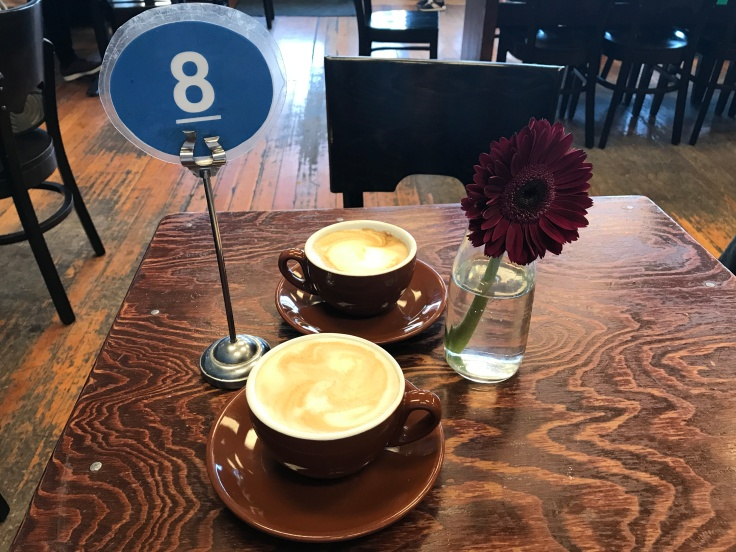 A Pair of Cappuccinos and a Fresh Daisy at Blue Dot Café & Coffee Bar in Alameda, California