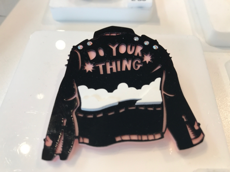 "A photo of the, ""Do Your Thing Jacket Brooch,"" from Tatty Devine. Tatty Devine is a local shop located in London, England. The pin is in the shape of the back of a black leather jacket that says, ""Do Your Thing,"" in pink writing above clouds. The brooch is made out of black acrylic and has sparkly Swarovski crystals on the shoulders of the jacket design."