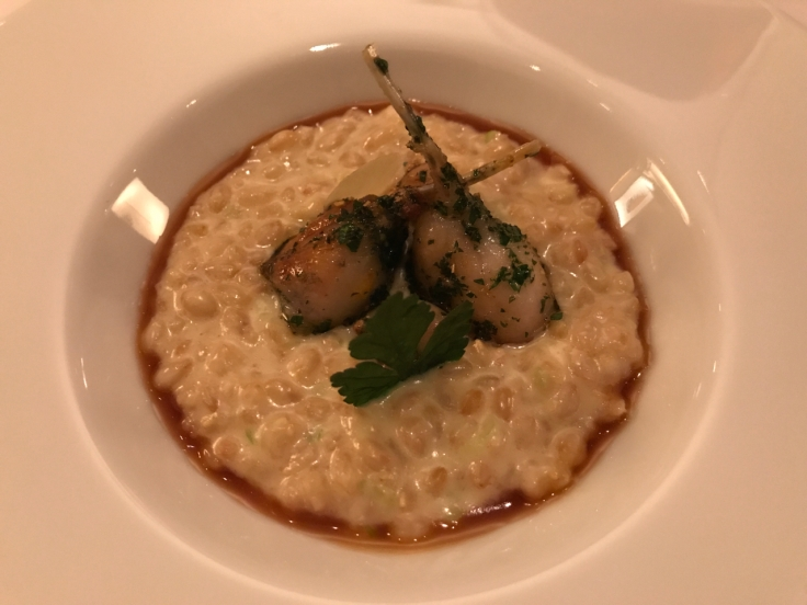 A photo of peautre du Pays de Sault cuisiné comme un risotto avec cuisses de grenouilles dorées (delicious spelt from the Pays de Sault region of France cooked risotto style and served with frog legs at Le Taillevent in Paris.