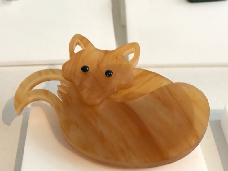 "A photo of the, ""Fox Brooch,"" from Tatty Devine. Tatty Devine is a local shop located in London, England. The pin is in the shape of a cute honey colored fox and is made out of acrylic."