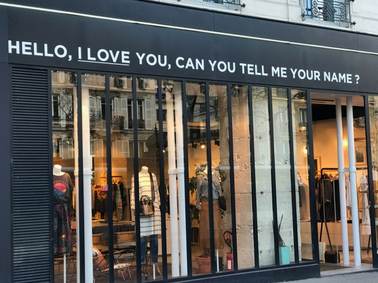 "A photo of the exterior of the Leon & Harper boutique on Boulevard Beaumarchais in Paris, France. A sign in the front reads, ""Hello, I love you, can you tell me your name?"""