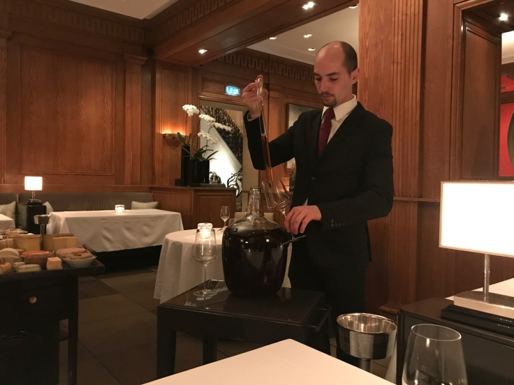 A photo of a sommelier serving port wine from the French side of southwest Andorra being served out of a giant glass jug and syringe at Le Taillevent in Paris, France.
