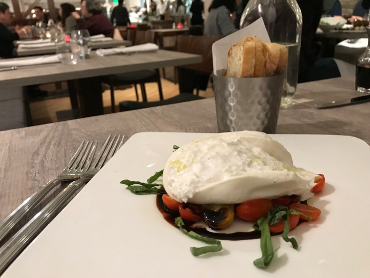 A photo of Morsey's Farm Burrata on the table at Morsey's Farmhouse Kitchen in Los Altos, California. The burrata is made from water buffalo milk and is served with tomato jam, olive oil, balsamic vinegar, basil and maldon salt.