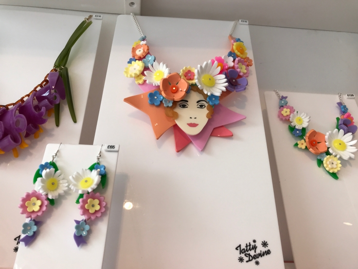 "A photo of the, ""May Flower,"" floral earrings and two of the, ""May Flower Queen,"" necklaces from Tatty Devine. Tatty Devine is a local shop located in London, England. The pretty plastic jewelry features white, yellow, baby blue and pink flowers."