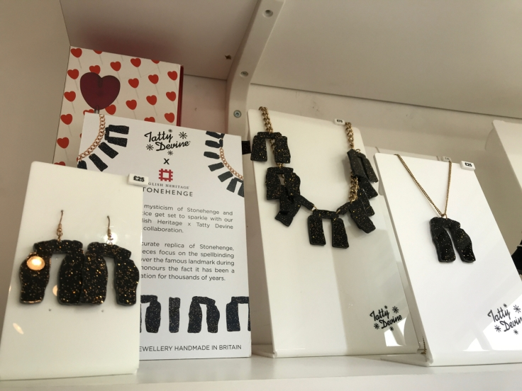 "A photo of pieces from the, ""Stonehenge,"" jewelry collection which was a collaboration between English Heritage and Tatty Devine. Tatty Devine is a local shop located in London, England. The pretty plastic jewelry features necklaces and earrings done in black acrylic and flecks of gold designed to look like Stonehenge."