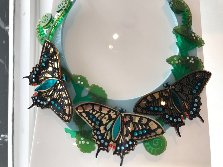 "A photo of the limited edition, ""Swallowtail Statement Necklace,"" from Tatty Devine. Tatty Devine is a local shop located in London, England. The necklace features iridescent butterflies in gold, blue and orange surrounded by green ferns. The butterflies are made out of Swarovski crystals and mirror acrylic. The necklace is in a collar shape."