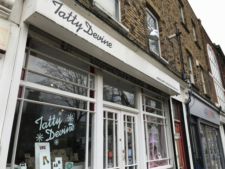 A photo of the exterior of Tatty Devine in London, England. The storefront of this little local shop on Brick Lane features colorful acrylic jewelry in its windows.