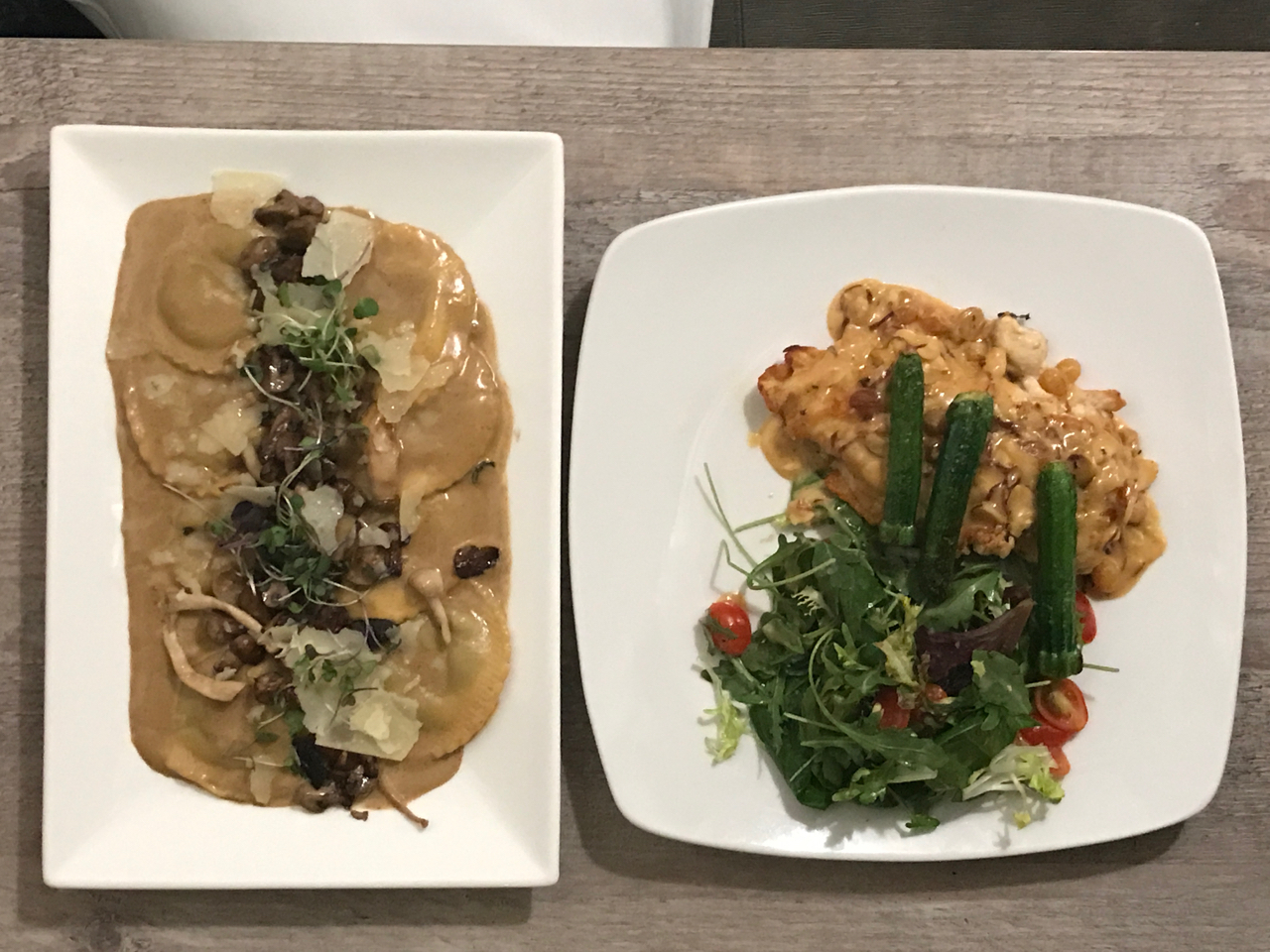 A photo of two dishes on the table at Morsey's Farmhouse Kitchen in Los Altos, California. The first dish is a wild mushroom ravioli and the second is a chicken paillard saltimbocca.