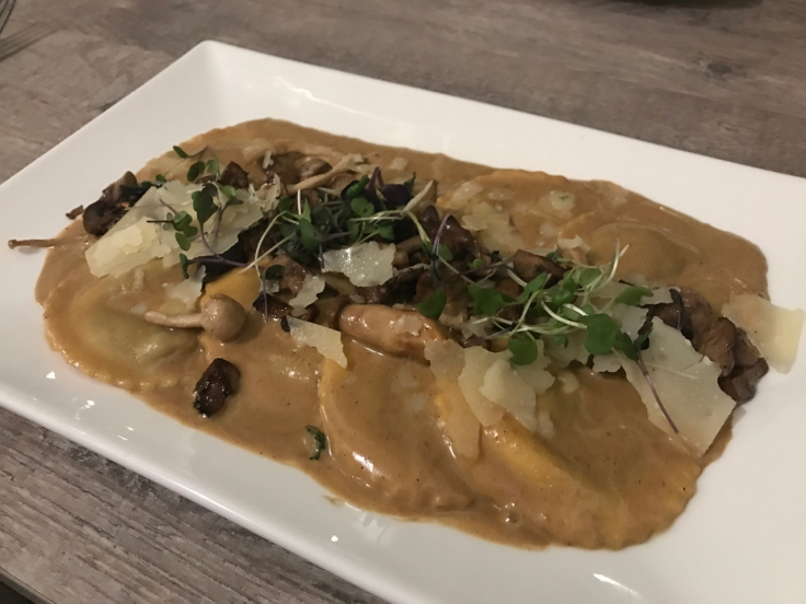 A photo of wild mushroom ravioli on the table at Morsey's Farmhouse Kitchen in Los Altos. The dish features a porcini buffalo cream sauce, shaved parmesan, micro greens and truffle.