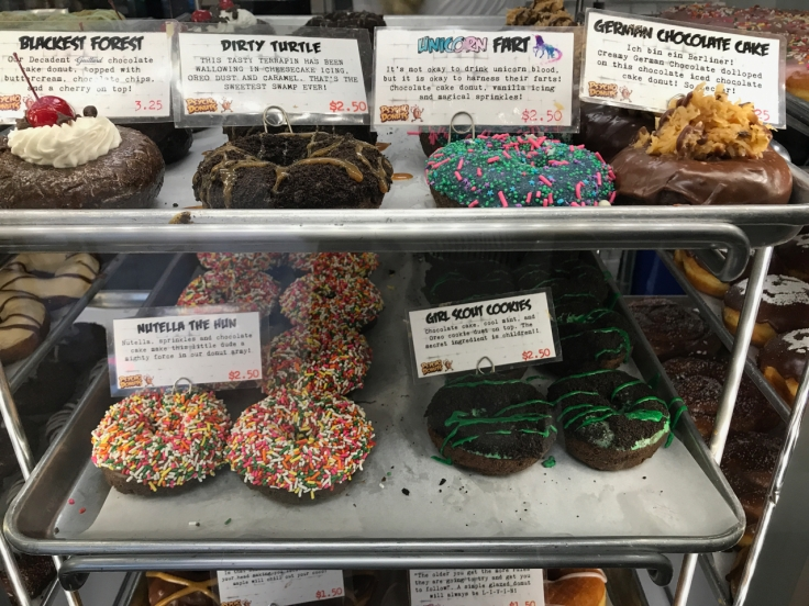 A photo of donuts on display at Psycho Donuts in Campbell, California including the blackest forest, dirty turtle, unicorn fart, German chocolate cake, Nutella the hun and Girl Scout Cookies donuts.