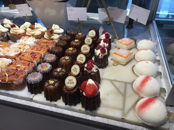 A photo of caramel canelés, vanilla canelés, strawberry canelés, exotic tarts and other pastries at Élan Café in London, England.