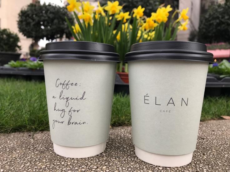 "A photo of two to-go coffee cups from Élan Café in London, England sitting outside in front of daffodils. One coffee cup reads, ""Coffee: A Liquid Hug for Your Brain,"" and the other cappuccino cup says, ""Élan Café."""