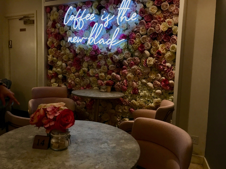 A photo of the tables near the rose flower wall inside Élan Café in London, England.
