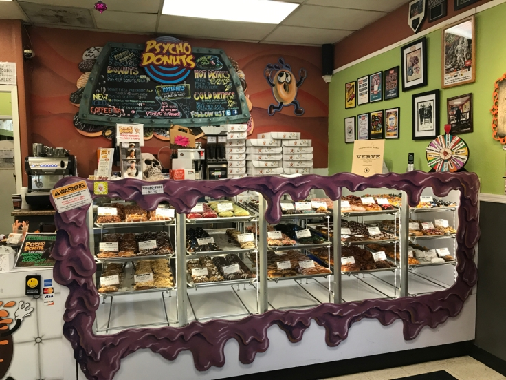 A photo of the wheel-o-donuts and the donut case at Psycho Donuts in Campbell, California.