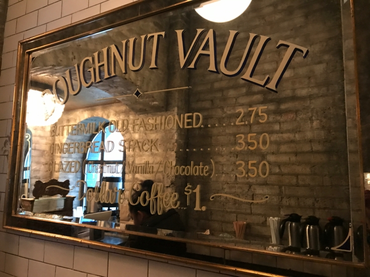 "A photo of a mirrored sign at the Doughnut Vault in Chicago, Illinois. The sign says, ""Doughnut Vault Buttermilk Old Fashioned $2.75 Gingerbread Stack $3.50 Glazed (Chestnut / Vanilla / Chocolate) $3.50 Dollar Coffee $1."""