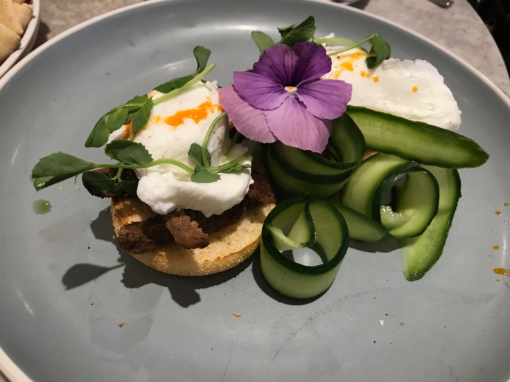 A photo of eggs on an English muffin topped with lamb merguez, cucumber and a purple flower at Élan Café in London, England.
