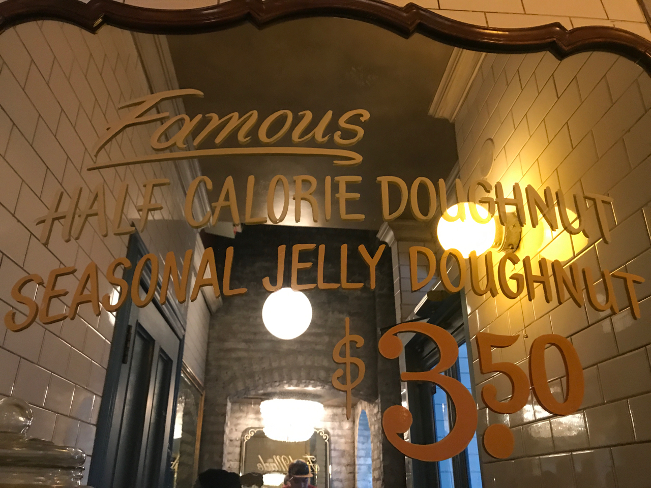 """A photo of a mirrored sign inside of the Doughnut Vault shop in Chicago, Illinois that says, """"Famous Half Calorie Doughnut Seasonal Jelly Doughnut $3.50."""""""