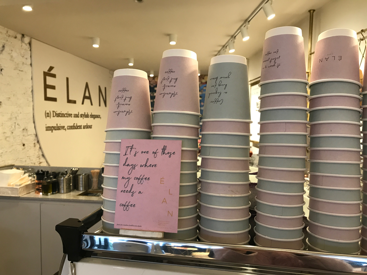 "A photo of the espresso machine at Élan Café in London, England. A stack of coffee cups with phrases like, ""Adventure Awaits, But First Coffee,"" ""Coffee a Liquid Hug for Your Brain"" and ""A Yawn is a Silent Scream for Coffee"" sits on top of the machine and there's a sign that says, ""It's One of Those Days Where My Coffee Needs a Coffee."""