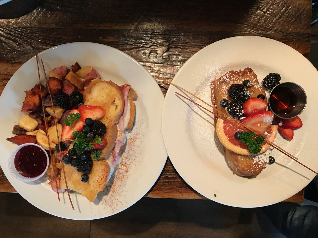 A photo of two plates on the table at Kitchen Story in San Francisco, California. The plate on the left features the KS Monte Cristo and the plate on the right has the Marscarpone Stuffed Deep Fried French Toast.