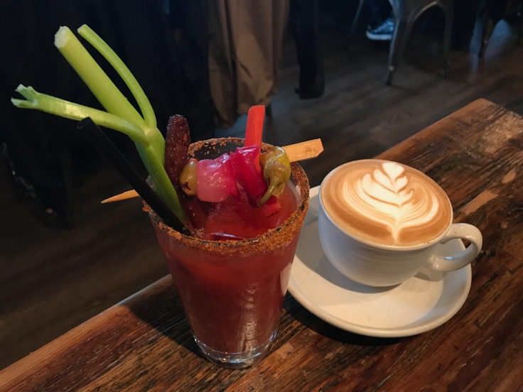 A photo of the millionaire's Mary Bloody Mary at Kitchen Story beside a cappuccino at Kitchen Story in San Francisco, California. The millionaire's Mary includes a a thick hunk of millionaire's bacon.