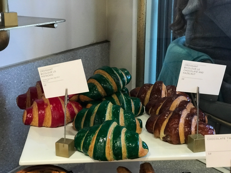 A photo of flavored croissants at Élan Café in London, England. The brightly hued pastries come in red, green and brown and in flavors like pistachio and chocolate hazelnut.