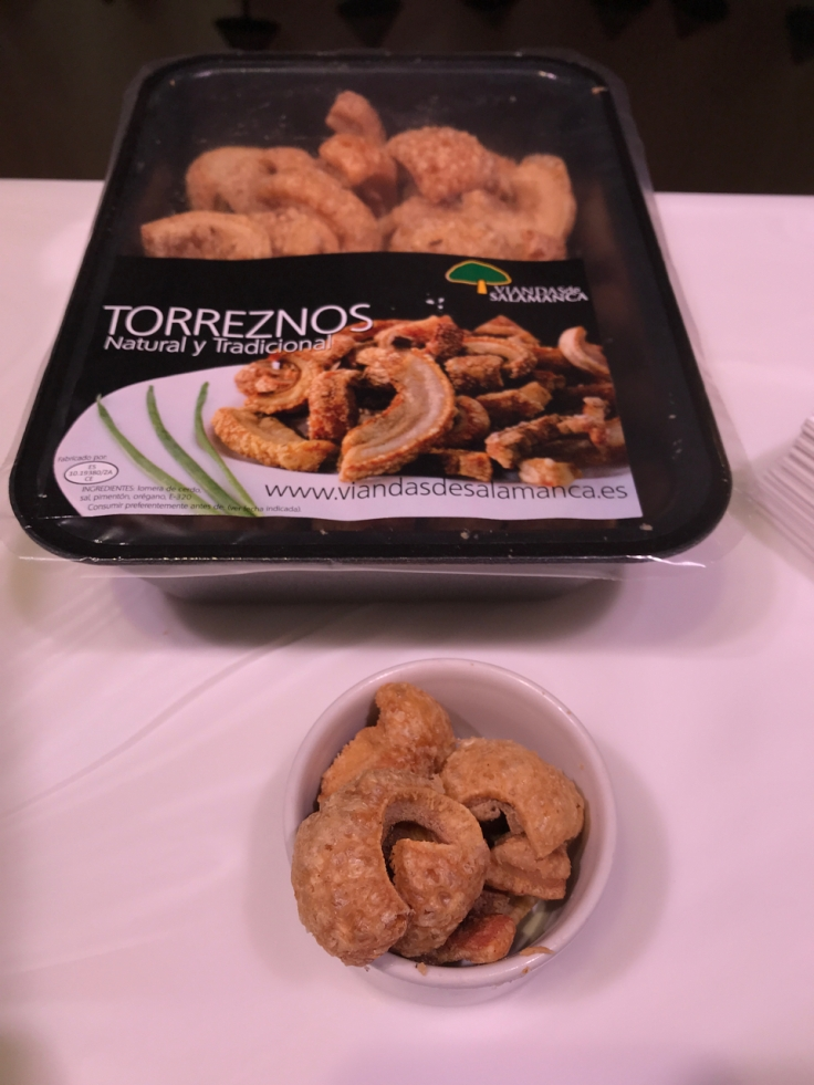 A photo of samples of torreznos on the counter at Viandas De Salamanca in London, England. Torreznos are fried bits of pork belly or pork rind commonly known as pork crackling in the United States.