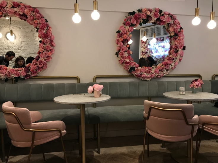 A photo of the inside of Élan Café in London, England replete with pink chairs. Roses adorn everything from the mirrors to the table tops at this picturesque British coffee shop.
