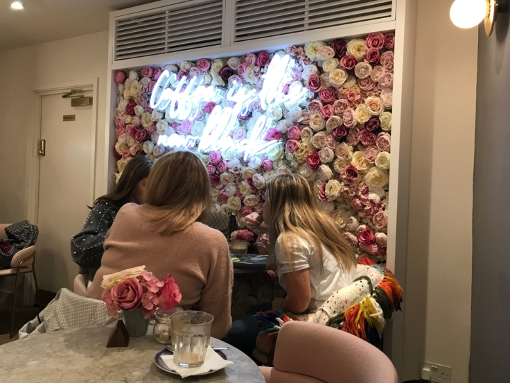 "A photo of three women sitting at a table downstairs in front of Élan Café's famed rose wall in London, England. A fluorescent sign lamp reads, ""Coffee is the New Black."""