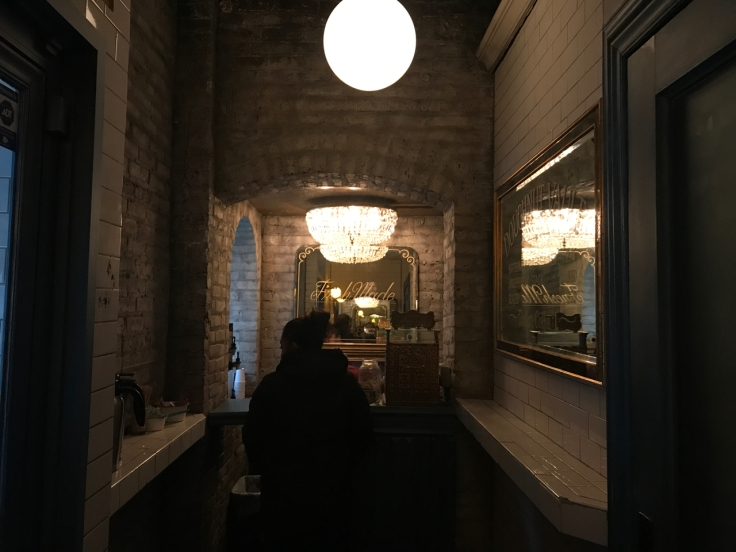 A photo inside the Doughnut Vault in Chicago, Illinois. The tiny donut shop space is decorated with subway tiles and is super small.