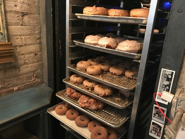A photo of trays of fresh warm donuts at Doughnut Vault in Chicago, Illinois.