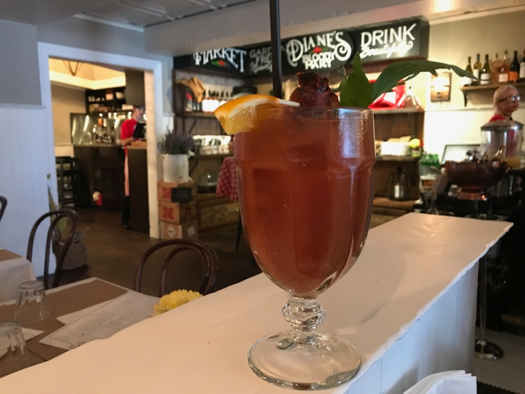 A photo of Diane's original mixer at Diane's Bloody Mary in San Francisco, California. The Diane's classic consists of garden ripe tomatoes, herb of lovage, olive brine, Tabasco, horseradish, vegan Worcestershire sauce, lemon, lime, a touch of honey and Tito's vodka.