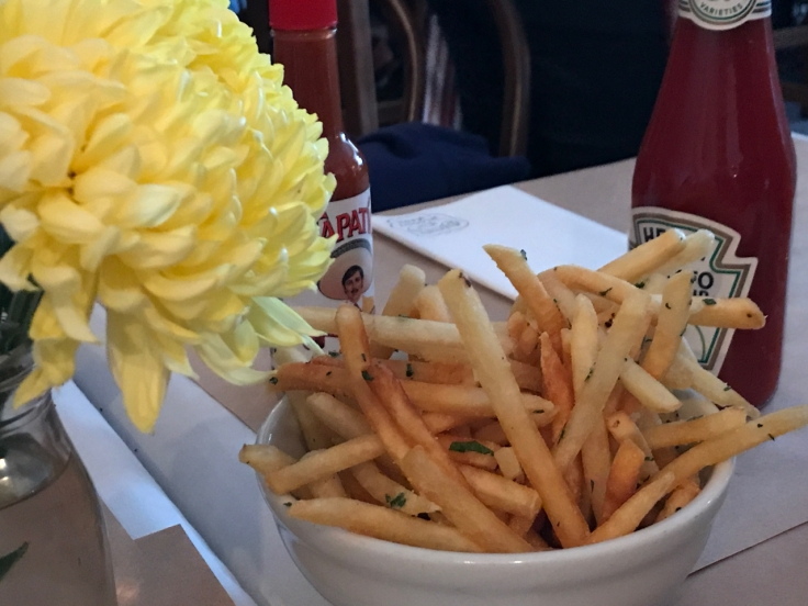 A photo of a bowl of the lovage fries sits on the table beside a yellow flower and Heinz ketchup at Diane's Bloody Mary in San Francisco.