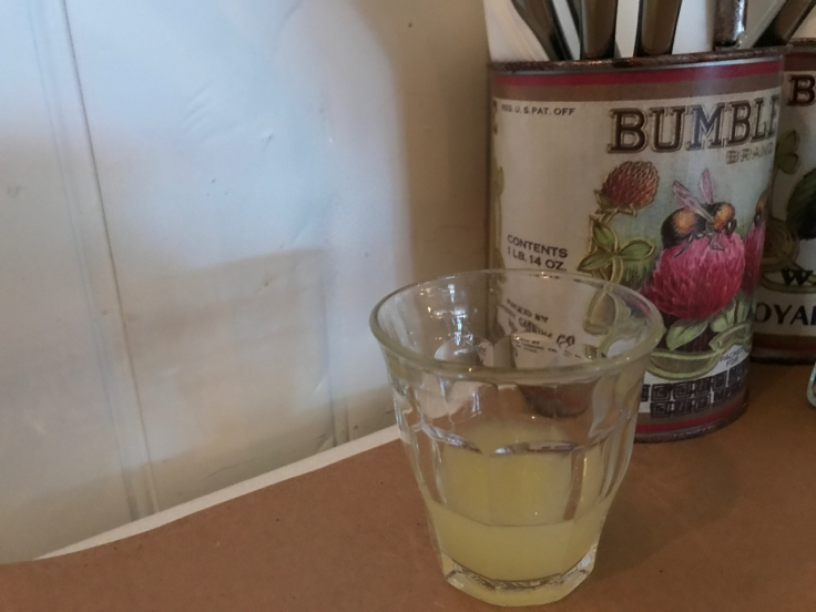 A photo of a shot glass filled with freshly squeezed chilled lemon juice on the table beside a Bumble Bee brand container filled with knives at Diane's Bloody Mary restaurant in San Francisco, California.