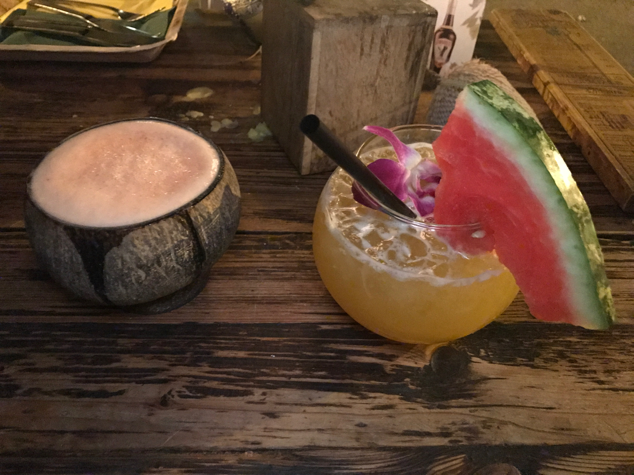 A photo of an African beer with guava in a coconut and the mama Africa drink at Ambiente Africa in Stuttgart, Germany. The mama Africa cocktail is made out of Dzama rum from Madagascar, coconut, melon liqueur, Triple Sec, orange, passionfruit and pineapple juice. (Mama Africa - Dzama rum, cocos, melonenlikör, Triple Sec, orangen, maracuja und ananassaff)