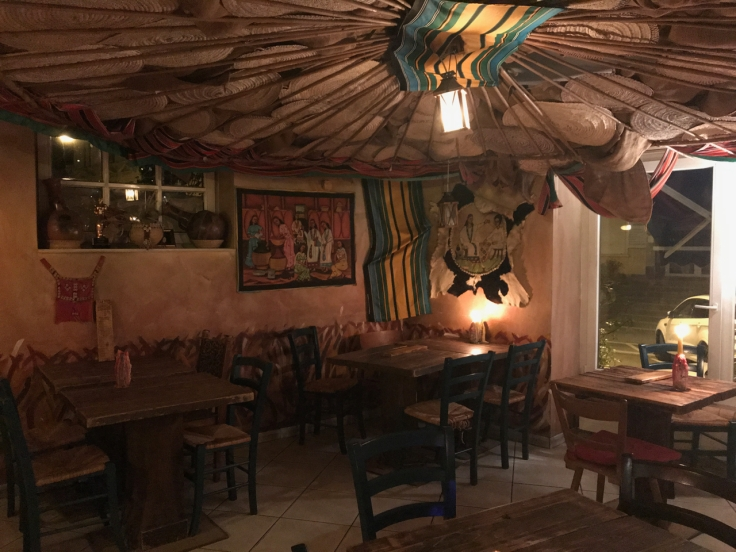 A photo of the inside dining room at Ambiente Africa in Stuttgart, Germany. There are colorful cushions and mats as well as embroidered goat skins and hand carved sculptures inside the restaurant.
