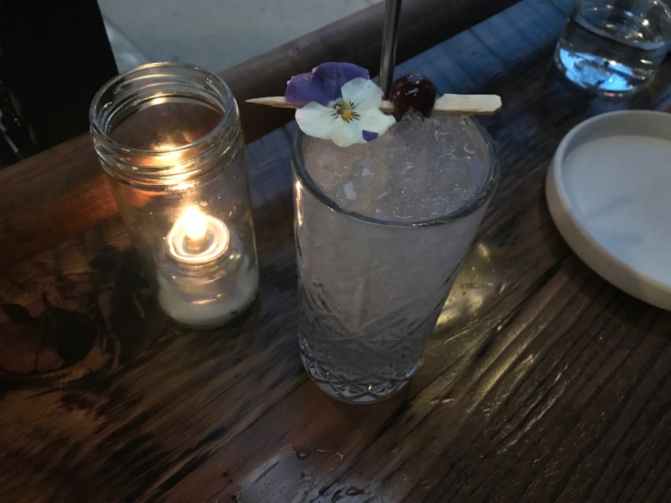 A photo of a candle set beside the aviation gin cocktail made with a candied flower, crème de violette, maraschino and lemon at The Snug SF in San Francisco, California.