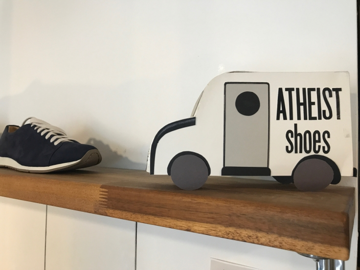 A photo of awfully black black sneakers and a little truck sign on a wood shelf at Atheist Shoes in Berlin, Germany.