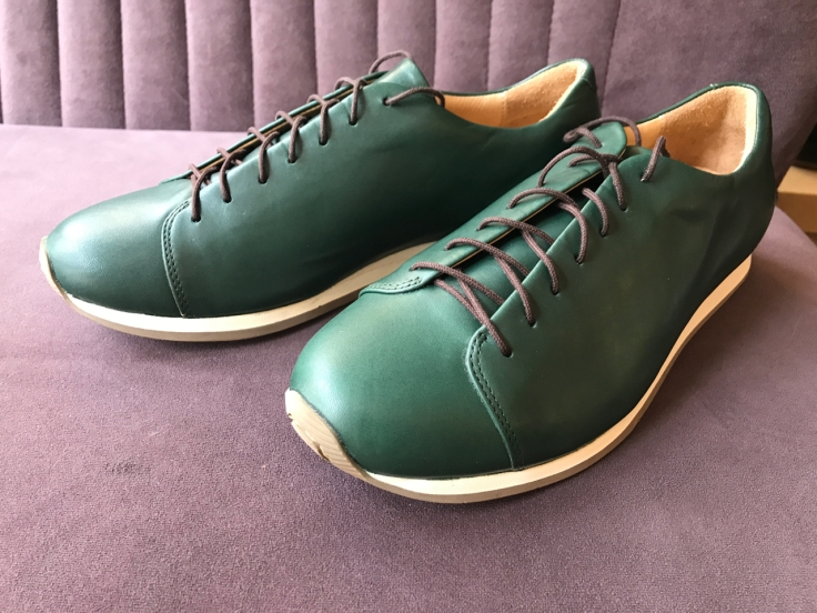A photo of British racing green sneakers at Atheist Shoes in Berlin, Germany.