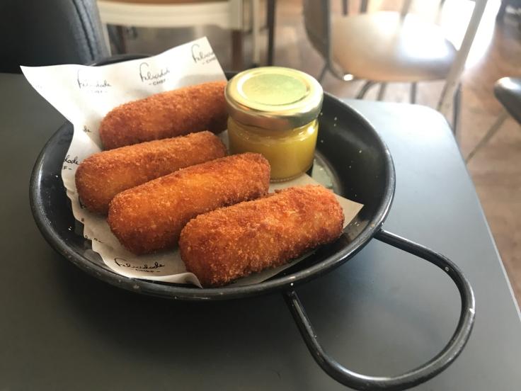 Four Iberian pork croquettes are served with mustard table side at Pharmacia restaurant in Lisbon, Portugal. (Croquete de presunto de porco preto com mostarda)