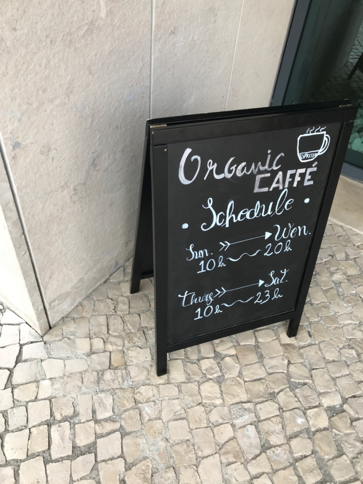 A photo of a sign outside the exterior of Organic Caffe in Estoril, Portugal. The sign has the schedule for the cafe written on it.