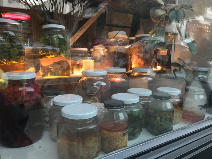 A photo of glass canning jars filled with prickly pear, raspberries and other goodies sitting in the front window of The Snug SF in San Francisco, California.